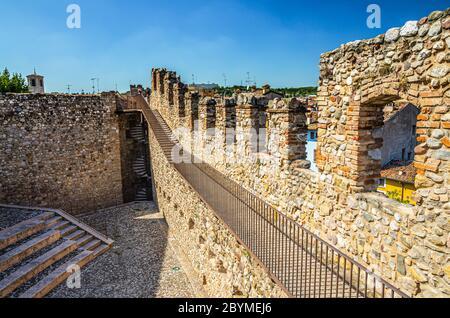 Desenzano del Garda, Italy, September 11, 2019: courtyard, spiral staircase and stone brick walls with merlons of medieval castle Castello di Desenzano, blue sky background - Stock Photo