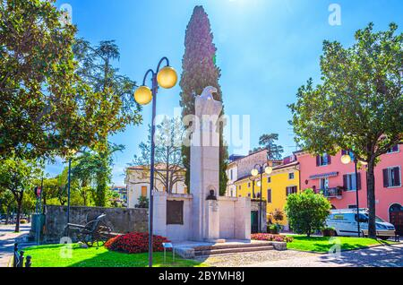 Desenzano del Garda, Italy, September 11, 2019: Achille Papa eagle monument and cannon on green grass lawn in historical town centre, blue sky background, Lombardy - Stock Photo