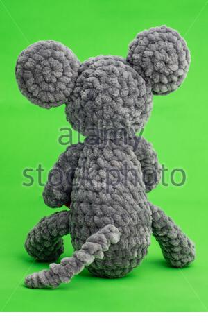 Grey knitted mouse with a heart in hand on a green background, rear view - Stock Photo