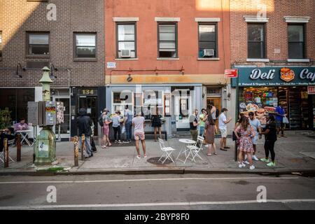 "Customers take advantage of relaxed liquor laws and ""grab and go"" cocktails outside a restaurant in Chelsea New York on Saturday, May 30, 2020. (© Richard B. Levine) - Stock Photo"