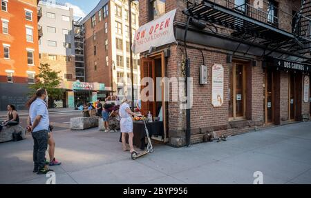 "Customers take advantage of relaxed liquor laws and ""grab and go"" cocktails outside a restaurant in the Meatpacking District in New York on Saturday, May 30, 2020. (© Richard B. Levine) - Stock Photo"