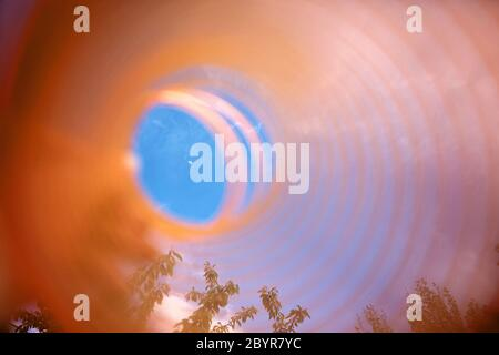 Abstraction, slinky toy held towards the sky, the moon seen through it - Stock Photo