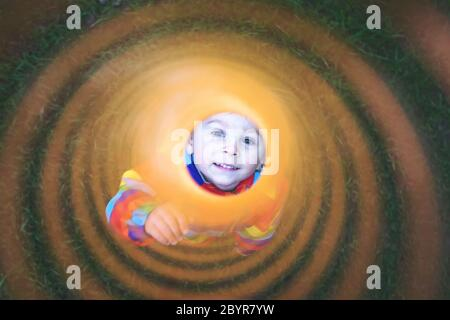 Cute toddler child, blond boy in colorful raincoat, holding slinky toy, dragging it from the camera away, creating interesting effect - Stock Photo