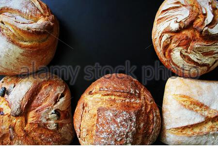 Bread. Assortment of different types of bread on a blackn background. Loaf, bun, baguette, cereal bread. Bakery products. - Stock Photo