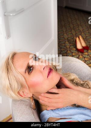 Vertical portrait of a sophisticated mature woman relaxing in an armchair - Stock Photo
