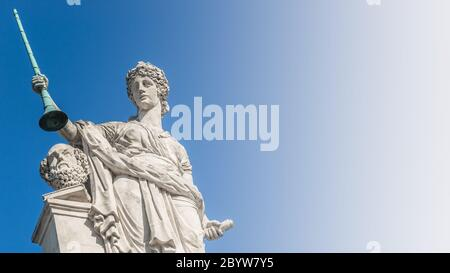 Old man head and Roman-Greek woman with pipe at the roof top in front of blue sky in Vienna, Austria - Stock Photo