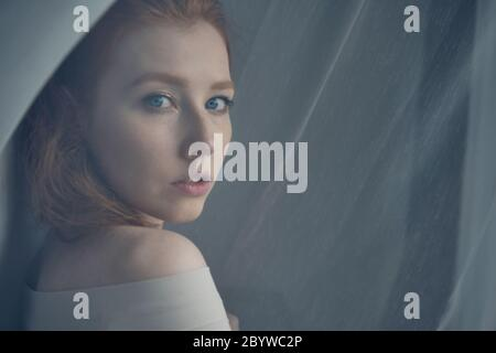 A red-haired girl with blue eyes stands in the midst of a translucent curtain and looks over shoulder, a view through the curtain.