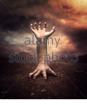 Strange human hand in the desert at night - Stock Photo