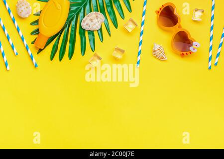 Swimming accessories - sunblock, heart - shaped glasses, ice cube, palm, shells, drinking paper straws for party with blue stripes isolated on yellow
