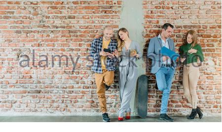 Team of people in startup company standing on brick wall in informal fashion - Stock Photo