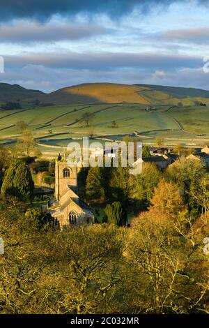 Burnsall - scenic sunlit Yorkshire Dales village in valley, church tower, upland fells, moors, fields & dark rain clouds (high view) - England, GB, UK