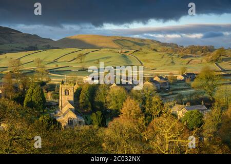 Burnsall - scenic sunlit Yorkshire Dales village in valley, church tower, cottages, upland fells, moors, fields & dark rain clouds - England, GB, UK.