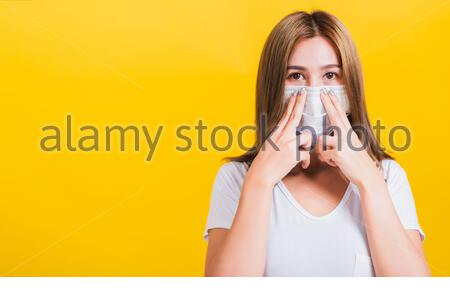 Portrait Asian beautiful young woman wearing face mask protect filter dust pm2.5 anti-pollution, anti-smog, COVID virus and air pollution her use hand - Stock Photo
