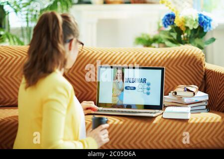 Seen from behind woman in yellow jacket in the living room in sunny day going to watch webinar on a laptop.