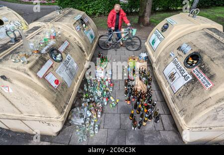Munich, Germany. 11th June, 2020. A man stands in front of dozens of glass bottles, sorted by colour, next to the overflowing containers at the roadside in the Haidhausen district. Credit: Peter Kneffel/dpa/Alamy Live News - Stock Photo