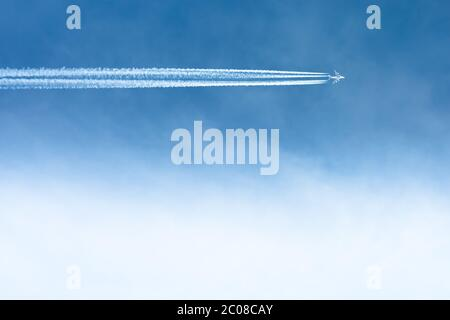A commercial airplane flying acrross the clear blue sky with clouds, and contrails. - Stock Photo