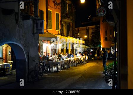 Late night in the village of Monterosso Al Mare, part of the Cinque Terre in Italy on the Italian Riviera as tourists enjoy an evening sidewalk cafe - Stock Photo