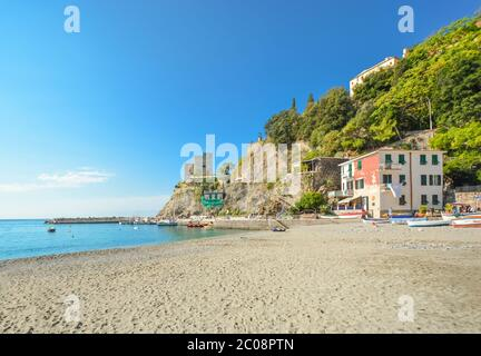The ruins of the Aurora Tower Castle at Monterosso al Mare rise above the sandy beach and coast in Cinque Terre Italy on the Ligurian Coast - Stock Photo