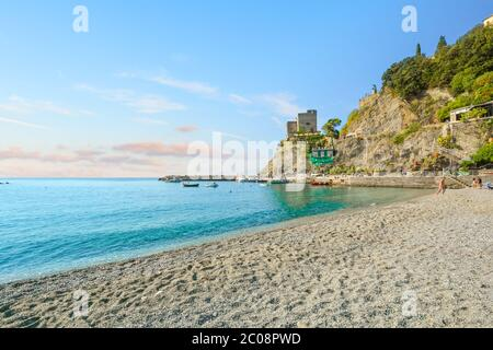 The ruins of the Aurora Tower and Castle at Monterosso al Mare rise above the sandy beach and coast in Cinque Terre Italy on the Ligurian Coast - Stock Photo