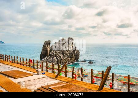 Umbrellas line the sandy beach of the Spiaggia di Fegina close to the large rock at the village of Monterosso al Mare Italy, part of the Cinque Terre - Stock Photo