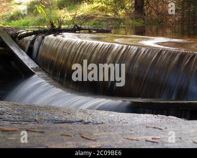 Small broken spillweir in the forest, long exposure - Stock Photo