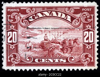 OTTAWA - CIRCA 1927:  Canadian postage stamp showing old fashioned wheat farming equipment pulled by horses, in Alberta with the Rocky Mountains in th - Stock Photo