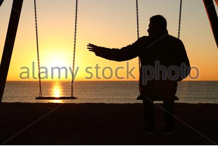 Back view backlighting silhouette of a man sitting on swing alone missing her partner at sunset on the beach in winter - Stock Photo