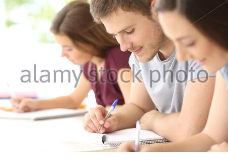 Close up of three students studying taking notes at classroom - Stock Photo