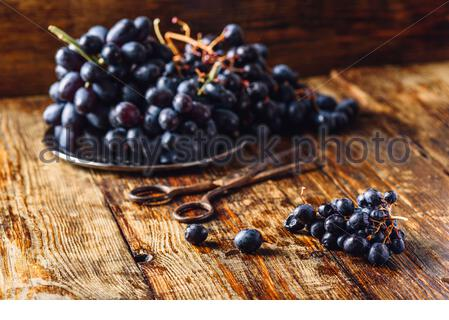Vine Grapes and Rusty Scissors on Wooden Surface. - Stock Photo