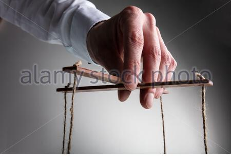 A Businessman's Hand Manipulating Marionette With String Against Gray Background - Stock Photo