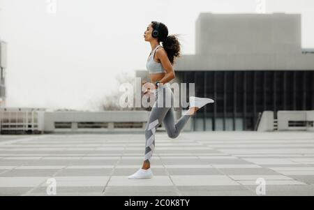 Full length shot of a healthy woman running in the city. Sporty woman exercising in the city.