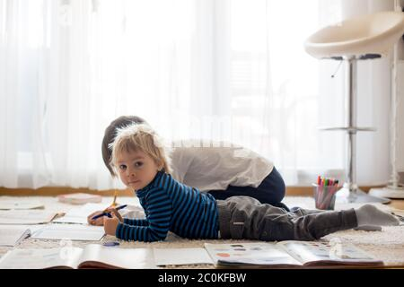 Child, doing school work on the floor at home while in quarantene, kid homeschooling - Stock Photo