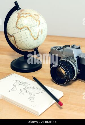 Camera, world globe and notebook with world map on a wooden desk. Travel concept image: planning a journey.