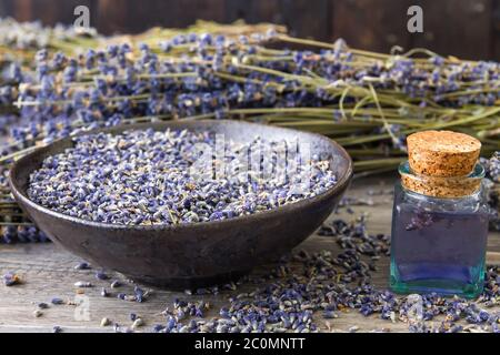 Lavender dried flowers and aroma in small bottle - Stock Photo