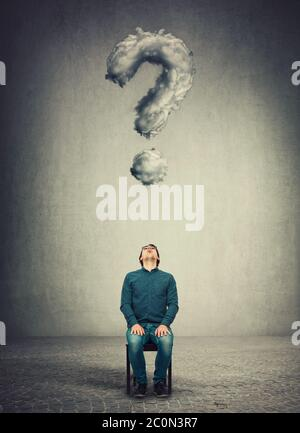 Businessman sitting on a chair, looks up astonished and pensive as a interrogation mark shaped cloud floats above his head. Stunned person staring upw - Stock Photo