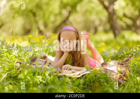 Happy little girl reading at the park - Stock Photo