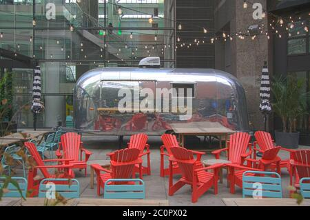 New York City Airstream Metallic caravan cafe business with outdoor seating in front of a glazed facade building in the big apple - Stock Photo
