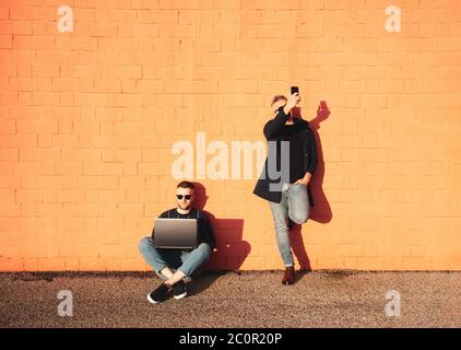 Two friends or colleagues with digital devices during lunch break - Young caucasian man sitting cross-legged on ground and working on laptop - The oth - Stock Photo