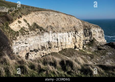 Crumbling cliffs in Dorset with rock strata on Jurassic Coast, with rough seas - Stock Photo