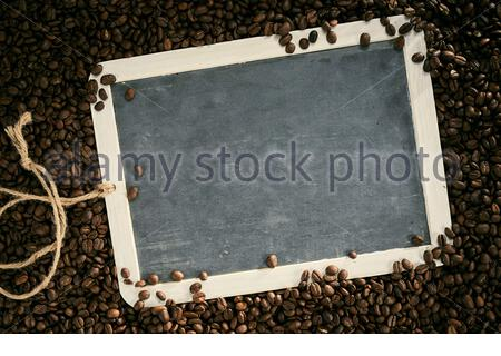 Roasted fresh aromatic coffee beans framing a blank vintage slate with cop space for your menu, recipe or advertising - Stock Photo