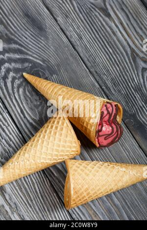 Strawberry ice cream in a waffle cone. Garnished with Chocolate. Nearby are empty waffle cones without ice cream. On pine boards painted in black and - Stock Photo