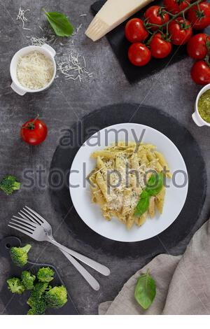 Traditional italian penne pasta with pesto, basil, tomatoes and parmesan. On a white plate, on a dark slate stand. Top view. - Stock Photo
