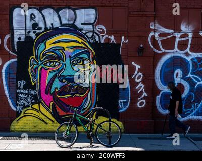 New York, New York, USA. 12th June, 2020. New York, New York, U.S.: a man walks past a George Floyd mural painted by street artist Fumero in East Village during the peaceful protests opposing systemic racism and police brutality. Credit: Corine Sciboz/ZUMA Wire/Alamy Live News - Stock Photo