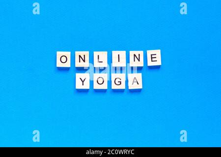 The word ONLINE YOGA written in wooden letterpress type on a blue background. top view. flat layout. - Stock Photo