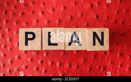 Wooden Blocks with the text: Plan on red leather background. Business planning management concept