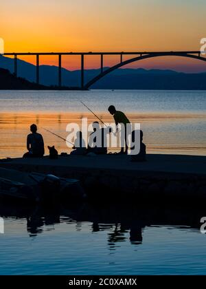 Family together dusk evening free time fishing bridge mainland to island Krk in background silhouettes silhouetting silhouette - Stock Photo