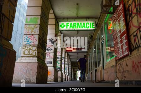 Bucharest, Romania - May 11, 2020 Illuminated advertisement of a pharmacy above the sidewalk that passes under a section of a building supported by ar - Stock Photo