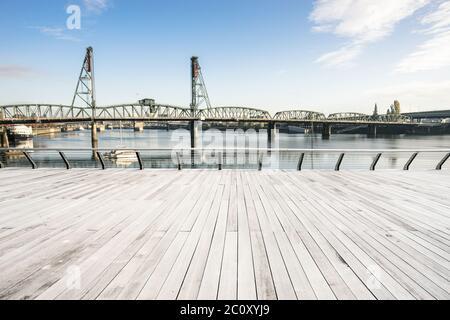 empty wood floor with steel bridge over sea in portland - Stock Photo
