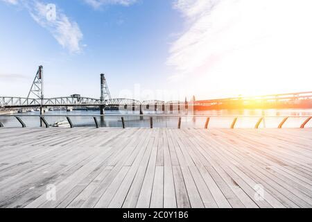 empty wood floor and bridge over water at sunrise in portland - Stock Photo