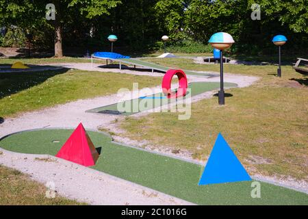 Mini golf, crazy golf course play with red and blue obstacles on a warm sunny day - Stock Photo
